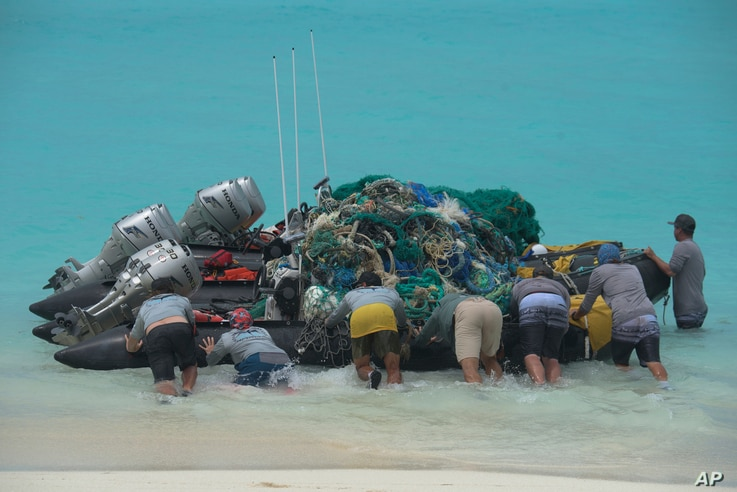 In this April 10, 2021 photo provided by Matthew Chauvin, workers with the Papahanaumokuakea Marine Debris Project push small…