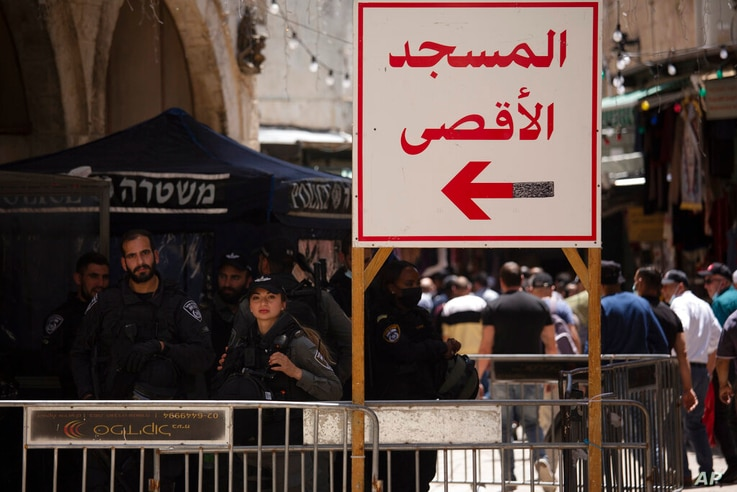 """Israeli police stand at a checkpoint with a sign in Arabic that reads, """"Al-Aqsa Mosque,"""" in the Old City of Jerusalem for…"""