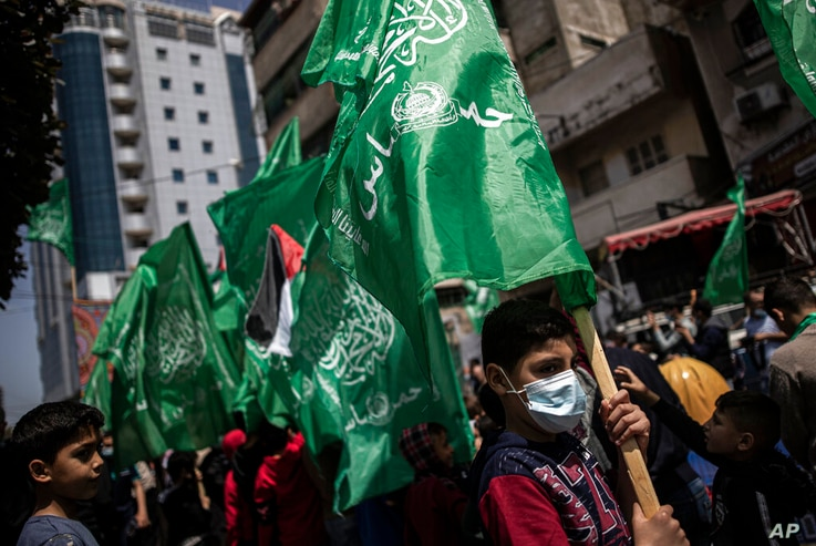 Palestinians hold Hamas movement green flags attend a protest in solidarity with Muslim worshippers in Jerusalem, in Gaza City,…