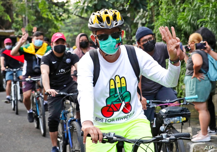 Activists ride their bicycles as they flash a three-finger salute of defiance during a rally called 'bike for Myanmar' against…