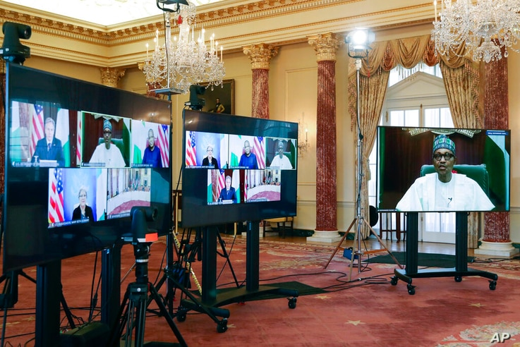 Nigeria's President Muhammadu Buhari appears on a screen, at right, as he speaks during a virtual bilateral meeting with…