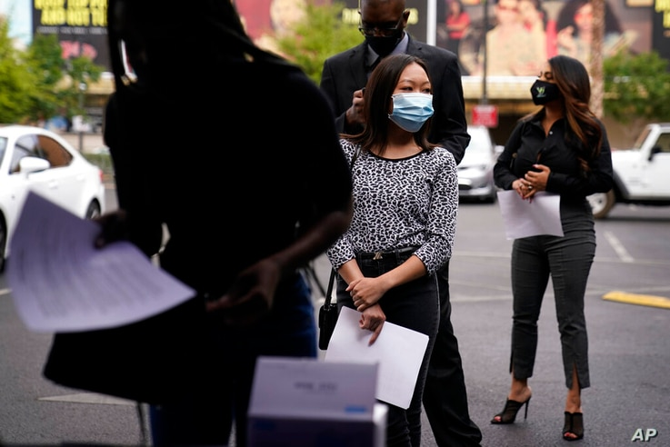 People wait in line, resumes in hand, while waiting to apply for jobs during an outdoor hiring event for the Circa resort and…