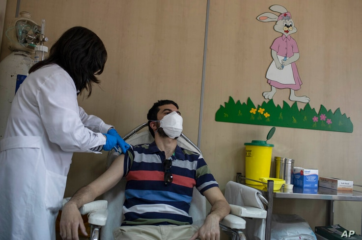 36 year-old Vasilis Tsipiras receives his first dose of the of the AstraZeneca COVID-19 vaccine, at a vaccination center in…