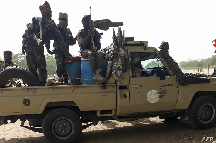 FILE - Soldiers of the Chad Army sit on the back of a Land Cruiser at the Koundoul market, 25 km from N'Djamena, Jan. 3, 2020, upon their return  after a months-long mission fighting Boko Haram in neighboring Nigeria.