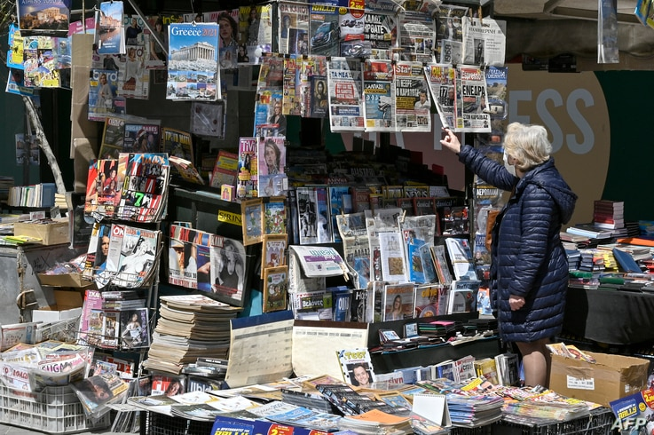 A woman reads newspapers headlines of the killing of a Greek journalist in Athens, April 10, 2021.