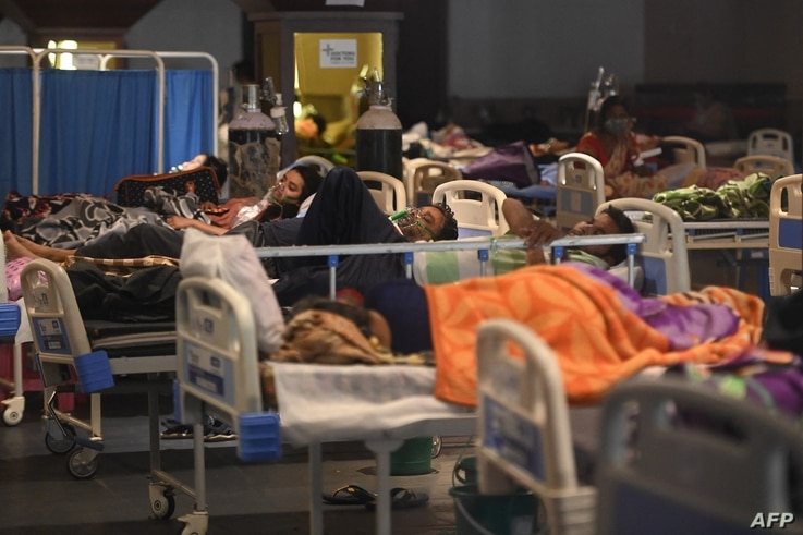 Patients breathe with the help of oxygen masks inside a banquet hall temporarily converted into a Covid-19 coronavirus ward in New Delhi, India, April 27, 2021.