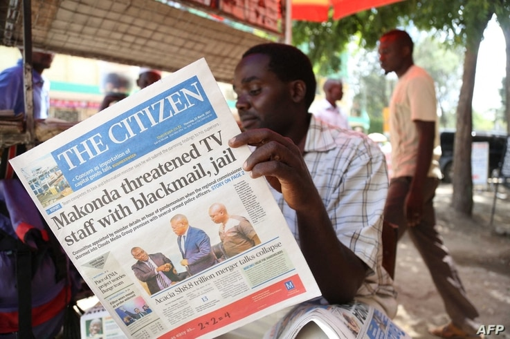 "FILE - A man reads the local English-written daily newspaper ""The Citizen"" in Arusha, northern Tanzania, March 23, 2017."
