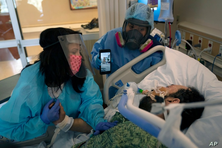 Patty Trejo, left, looks at her intubated husband, Joseph, in a COVID-19 unit at St. Jude Medical Center, in Fullerton, California, Feb. 15, 2021.