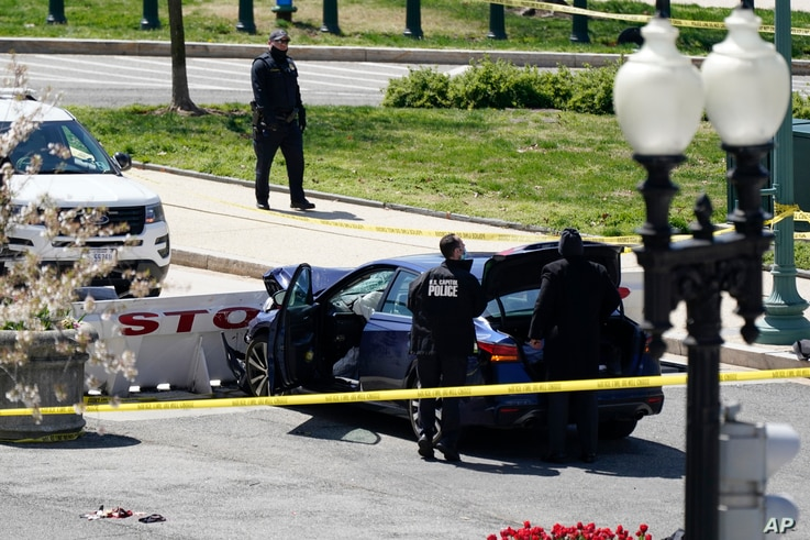 U.S. Capitol Police officers stand near a car that crashed into a barrier on Capitol Hill in Washington, April 2, 2021.