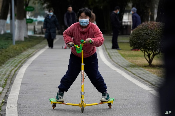 FILE - A child wearing a mask rides on a skate scooter in Wuhan in central China's Hubei province, Jan. 29, 2021.