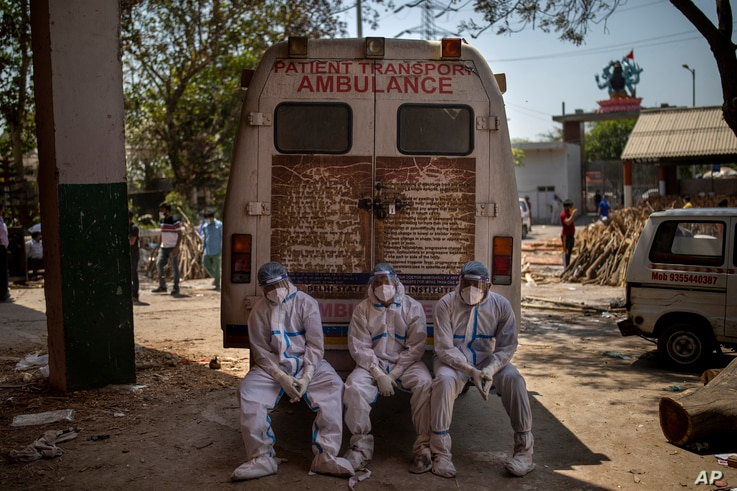 Exhausted workers, who bring dead bodies for cremation, sit on the rear step of an ambulance inside a crematorium, in New Delhi, India, April 24, 2021.