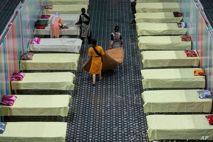 Workers arrange beds at a COVID-19 treatment facility newly set up at an indoor stadium in Gauhati, India, April 19, 2021.