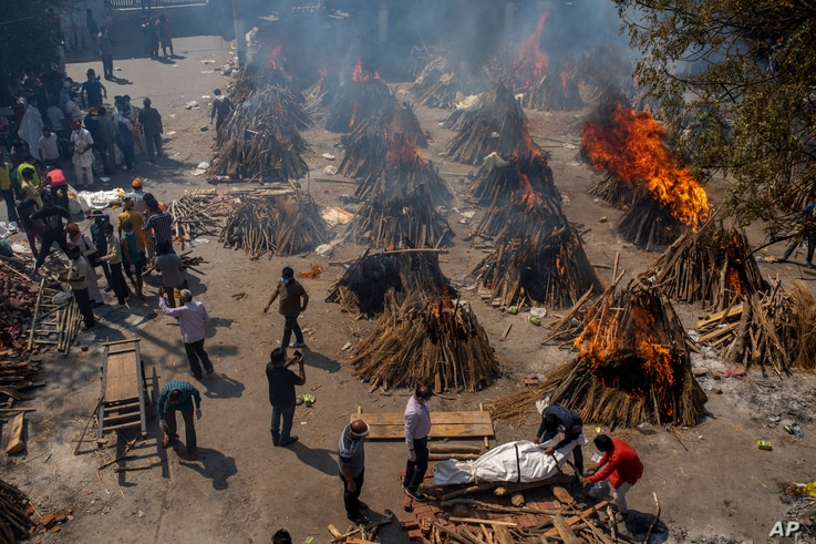 Multiple funeral pyres of COVID-19 victims burn at a site that has been converted into a mass crematorium, in New Delhi, India, April 24, 2021.