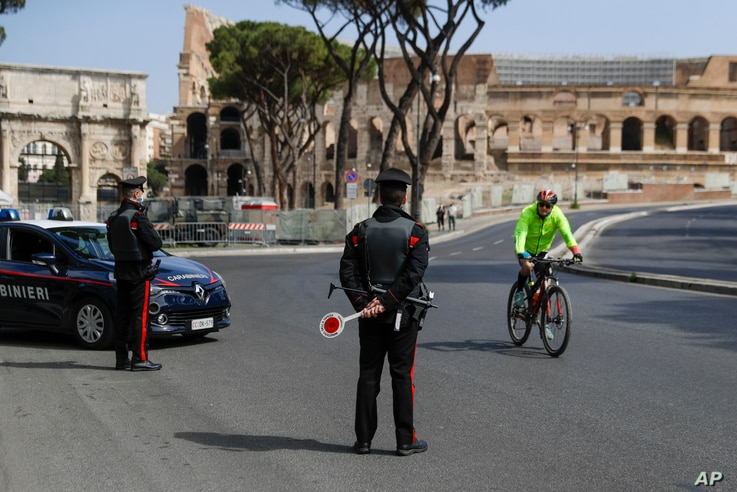 A cyclist rides past Carabinieri police officers at a road block near the Colosseum, in downtown Rome, April 3, 2021. Italy went into lockdown on Easter weekend in its effort to battle the COVID-19 pandemic.