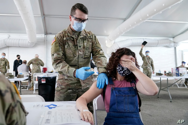 Leanne Montenegro covers her eyes while she receives the Pfizer COVID-19 vaccine at a FEMA vaccination center at Miami Dade College, April 5, 2021, in Miami, Florida.
