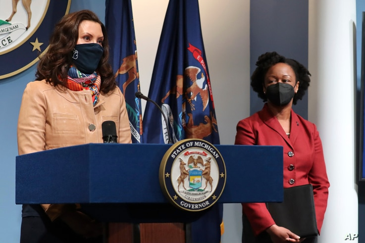 Governor Gretchen Whitmer addresses the state as Michigan Department of Health and Human Services Chief Medical Executive Dr. Joneigh Khaldun, right, listens, April 9, 2021, in Lansing.