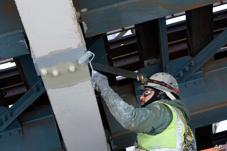 A painter works on steel support beams underneath the Manhattan Bridge, part of New York's aging infrastructure, April 6, 2021.