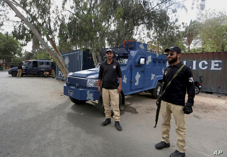 Police officers guard a road blocked with shipping containers, near the French consulate, in Karachi, Pakistan, April 15, 2021.