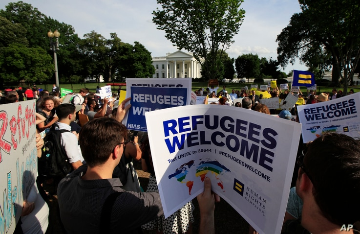 FILE - Activists hold signs in front of the White House during a rally in support of increased refugee admissions to the U.S., in Washington, June 20, 2017.