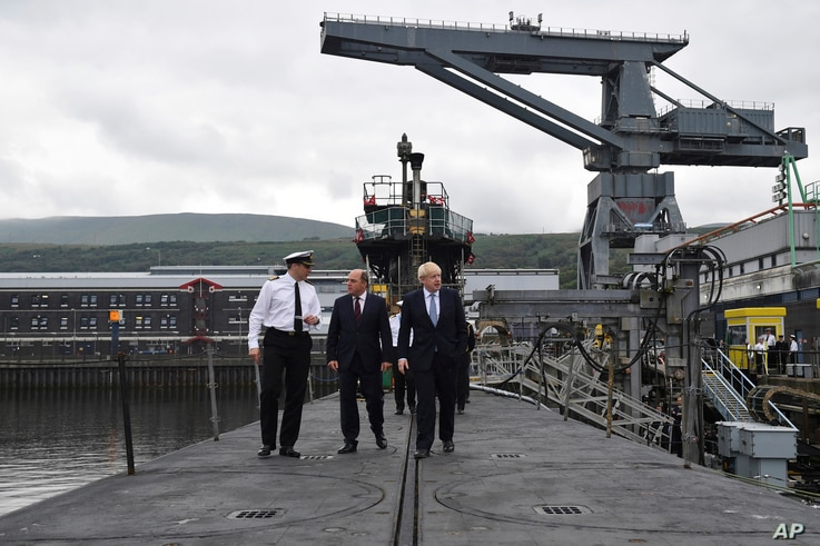 FILE - Britain's Prime Minister Boris Johnson, right, visits the nuclear submarine HMS Victorious with Defence Secretary Ben Wallaceat, centre, and Commander Justin Codd, left, at the Naval Base in Faslane, Scotland, July 29, 2019.
