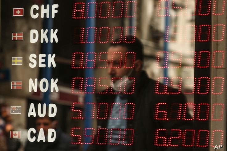 A man is reflected at a foreign currency board in a currency exchange shop, in Istanbul, Turkey, March 22, 2021.