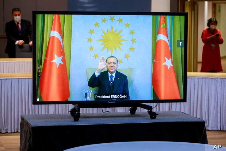 Turkey's President Recep Tayyip Erdogan waves from the video monitor as he participates in a video conference with European Commission President Ursula von der Leyen and European Council President Charles Michel in Brussels, March 19, 2021.