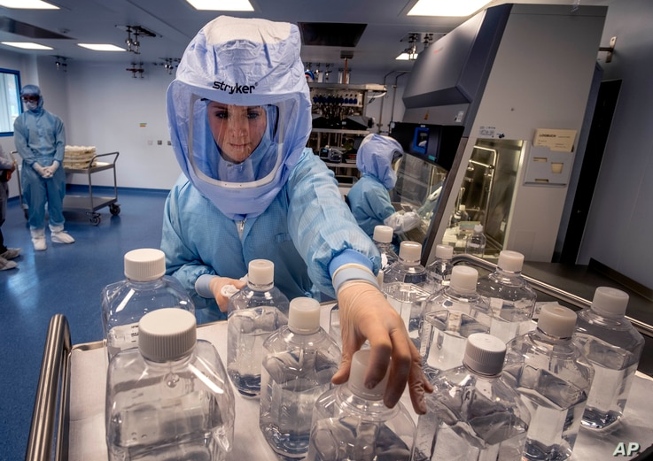 FILE - A laboratory worker simulates the workflow in a cleanroom of the BioNTech Corona vaccine production facility in Marburg, Germany, during a media day, March 27, 2021.