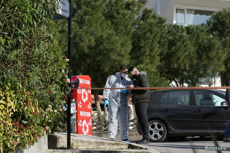 Forensic experts are seen at the site where Greek journalist George Karaivaz was fatally shot, in Athens, Greece, April 9, 2021.