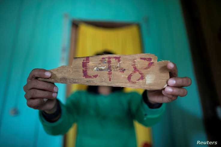 FILE - An indigenous woman of the Uru-eu-wau-wau tribe shows a piece of wood with a lot number removed from an area deforested by invaders in the village of Alto Jaru, at the tribe's reservation, near Campo Novo de Rondonia, Brazil, Feb. 1, 2019.