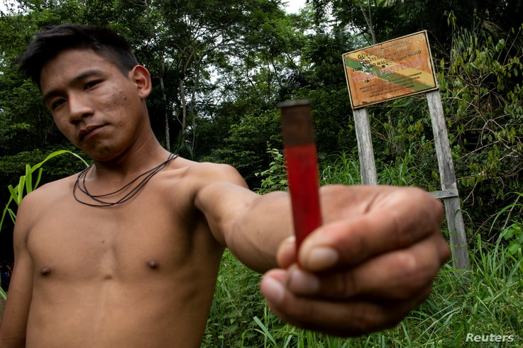 An indigenous man of the Uru-eu-wau-wau tribe shows the casing of a shell which had been fired into a sign, which warns of the limits of the tribe's reservation, near Campo Novo de Rondonia, Brazil, Jan. 31, 2019.