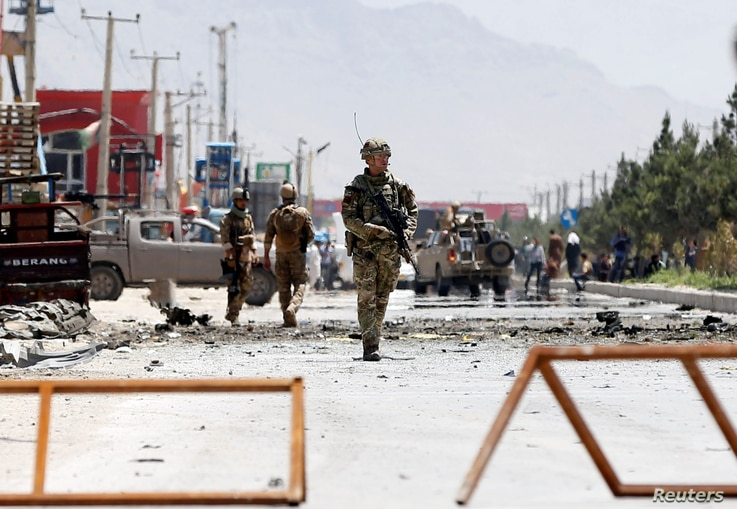 FILE - Afghan security forces and a British soldier with NATO-led Resolute Support Mission stand guard at the site of a suicide attack in Kabul, Afghanistan, May 31, 2019.