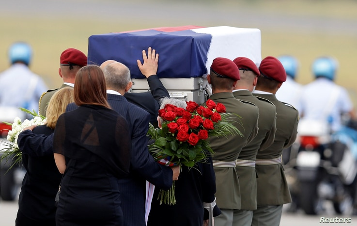 FILE - Relatives of three Czech soldiers, who were killed by a suicide bomber in eastern Afghanistan, mourn at the Vaclav Havel Airport in Prague, Czech Republic, Aug. 8, 2018.