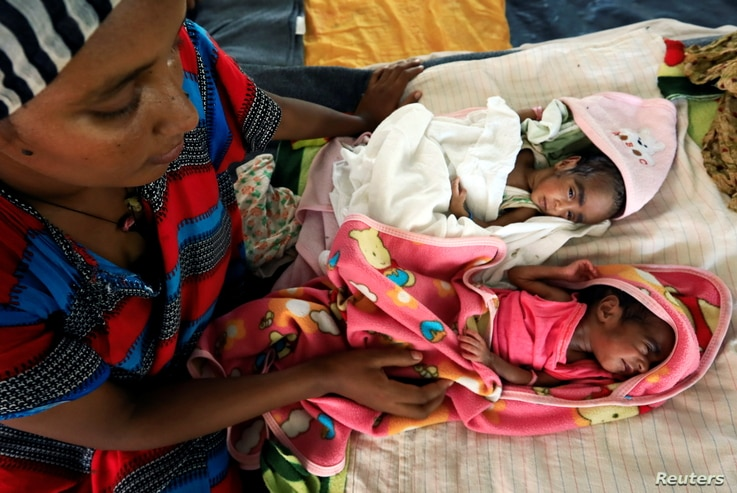 An Ethiopian woman who fled the ongoing fighting in Tigray region, nurses her newly born children inside a clinic in the Hamdayat camp on the Sudan-Ethiopia border, in eastern Kassala state, Sudan, Dec. 15, 2020.