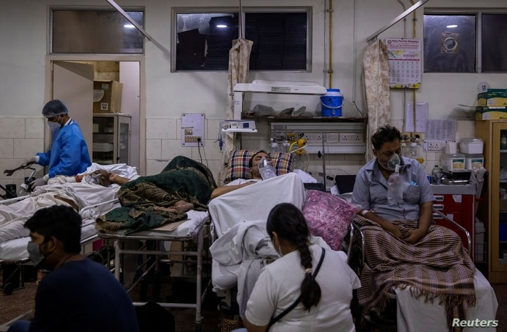 Manika Goel, sits next to her husband who is suffering from the COVID-19 inside the emergency ward at Holy Family hospital in New Delhi, India, April 29, 2021.
