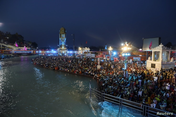 Devotees gather for an evening prayer on the banks of the Ganges river during Kumbh Mela, or the Pitcher Festival in Haridwar, India, April 12, 2021.