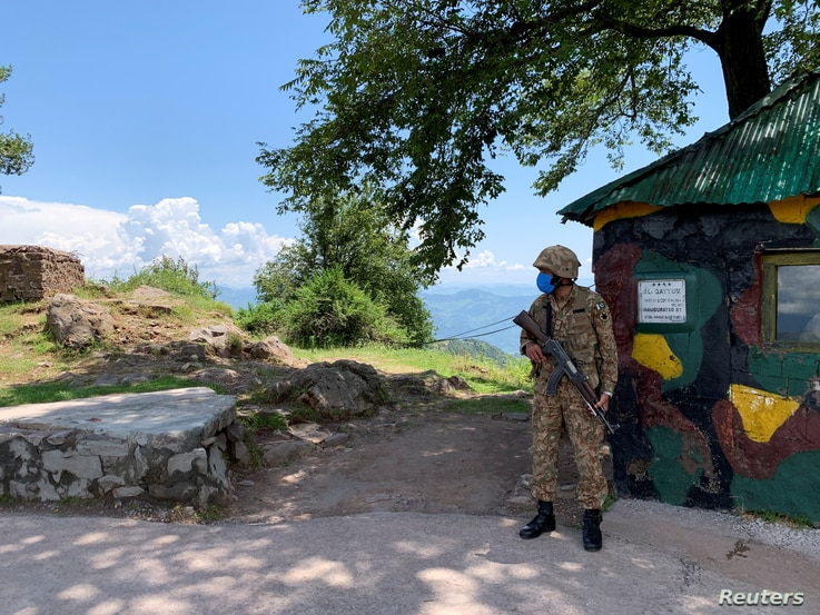 FILE - A Pakistan Army soldier stands guard at a hilltop post near the Line of Control (LoC) in Charikot Sector, Kashmir, July 22, 2020.