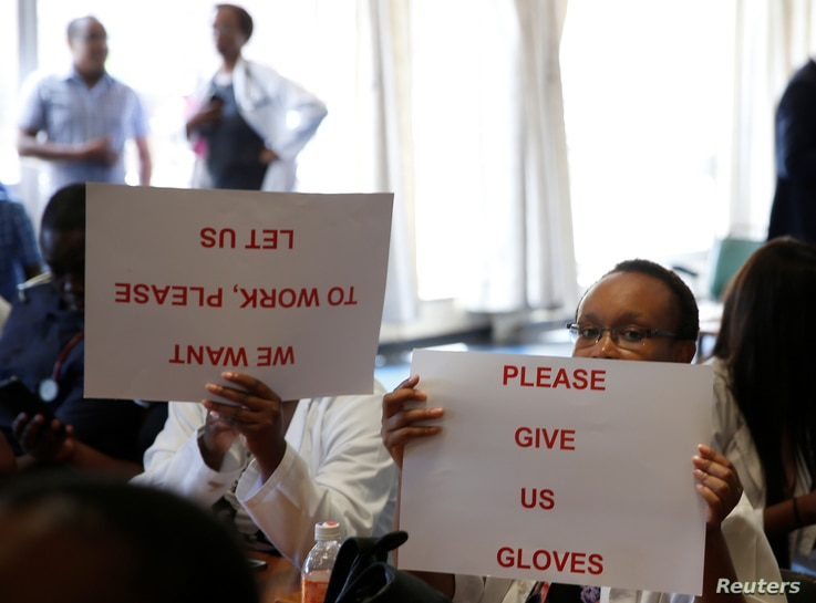 Senior doctors at Parirenyatwa General Hospital, Zimbabwe's biggest medical center, hold placards during a  demonstration to protest a lack of medicines, gloves and bandages in Harare, March 13, 2019.