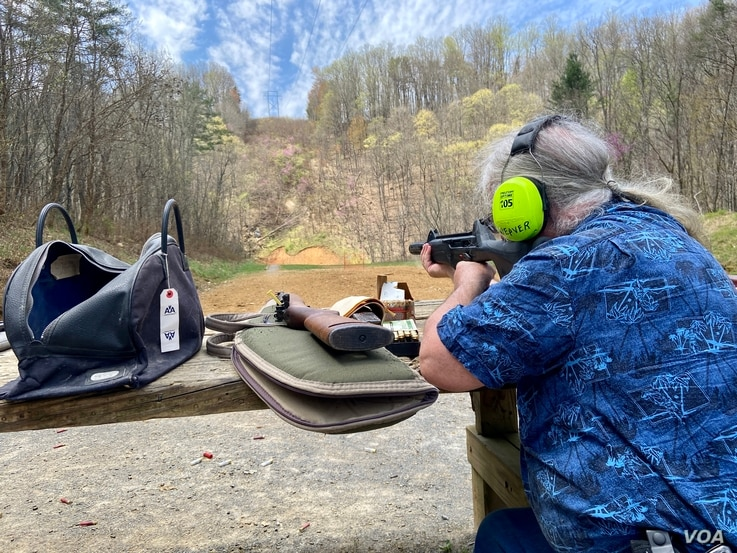 "Gun enthusiast Rob Weaver steadies his gun for target practice. Weaver, a former owner of a gun range in Maryland, is against gun regulations, saying the gun is not the problem. ""The problem is people who have ill intent, doing bad things."" (Carolyn Presutti/VOA)"