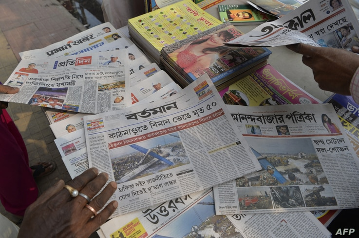 An Indian vendor arranges newspapers reporting the US-Bangla Airlines plane crash in Nepal at a newspaper stand in Siliguri on…