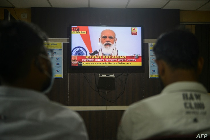 Journalists watch on a television India's Prime Minister Narendra Modi address to the nation, at a journalist club in Siliguri…