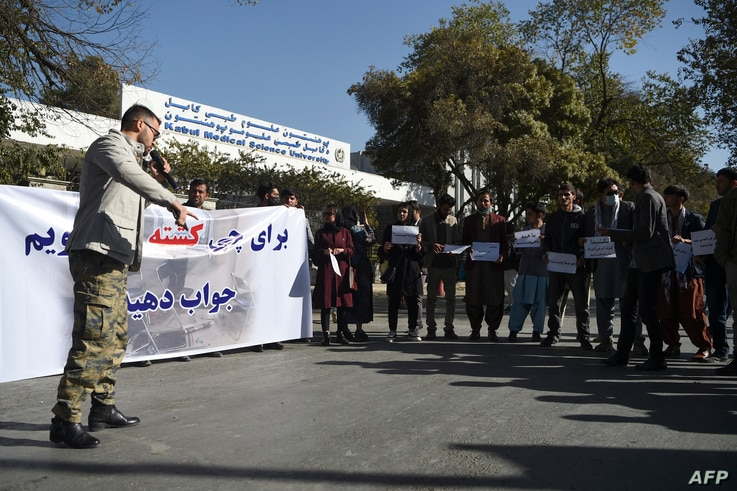 Students and civil society activists hold banners in protest as they shout slogans, a day after gunmen stormed Kabul university…