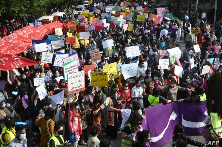 Activists of the Aurat March carry placards as they march during a rally to mark International Women's Day in Lahore on March 8…