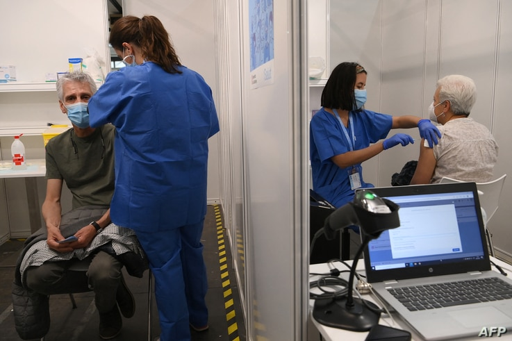 People receive a dose of the AstraZeneca's Covid-19 vaccine at a vaccination center on April 26, 2021 in Barcelona amid a...