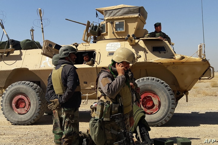 Afghan security forces stand near an armoured vehicle during ongoing fighting between Afghan security forces and Taliban...