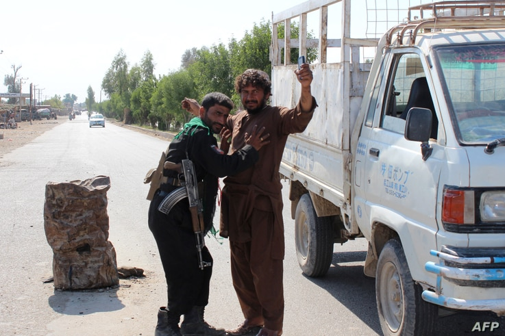 An Afghan policeman searches a man at a road checkpoint during the ongoing fighting between Afghan security forces and Taliban...