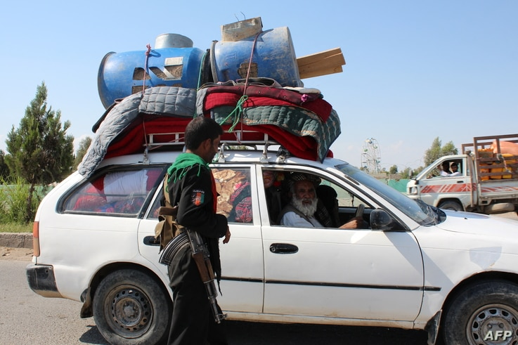 A policeman stands guard at a road checkpoint as an internally displaced family flees from the ongoing fighting between Afghan…
