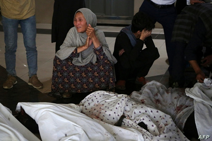 EDITORS NOTE: Graphic content / Family members and relatives mourn inside a hospital while sitting next to the bodies of…
