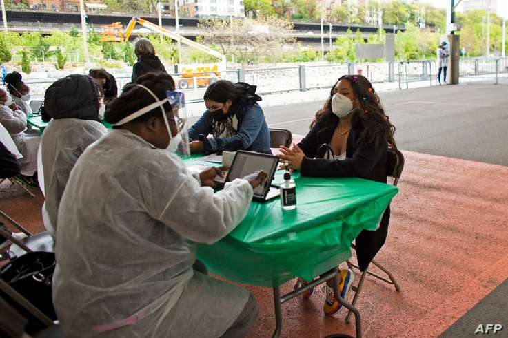 People check-in at a Covid-19 vaccination site at a sports center in Brooklyn, New York on May 8, 2021. (Photo by Kena Betancur…