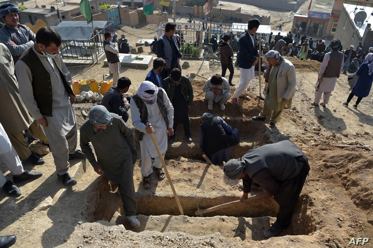 Shiite mourners and relatives dig graves for girls, who died in yesterday's multiple blasts outside a girls' school, during the…