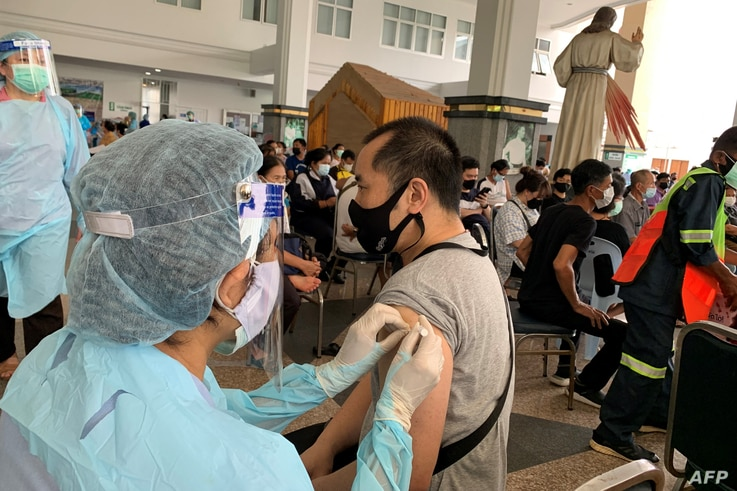 A medical personnel administer the Covid-19 coronavirus vaccination to a man at the Holy Redeemer Catholic church compound in...